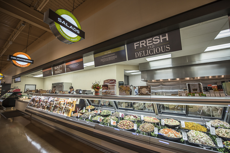 A deli section with a fresh and delicious sign.
