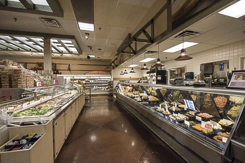 A deli counter next to a salad bar.