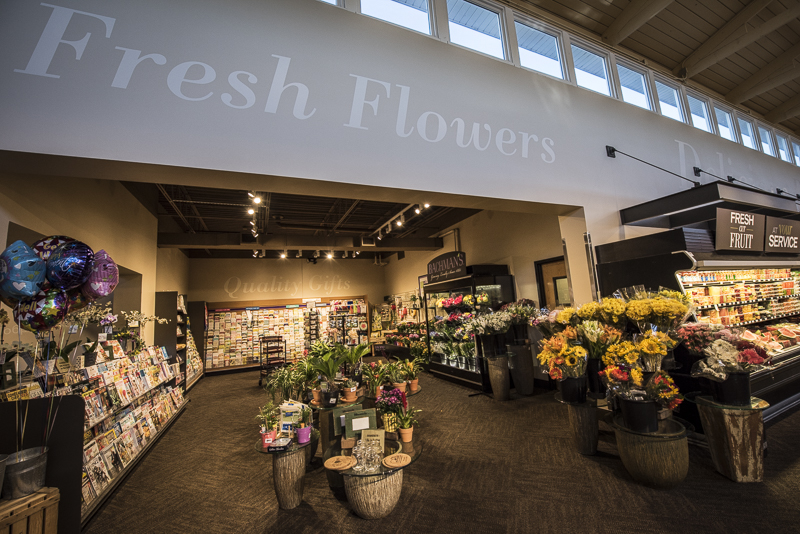 A floral section and gift section full of fresh flowers and racks of grift cards.